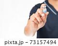 医師が手に持っている新型コロナワクチンのイメージ 73157494