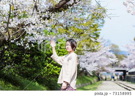 京都観光で蹴上のインクラインで桜を見ている女性 73158995