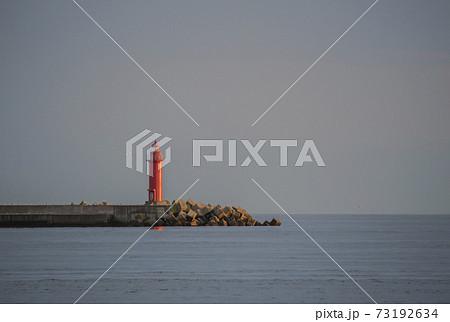 穏やかな夕暮れの港に立つ赤い灯台 73192634