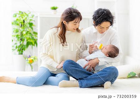 赤ちゃんにミルクをあげる夫婦 73200359