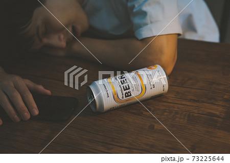 缶ビールを飲んで酔いつぶれる若者 73225644