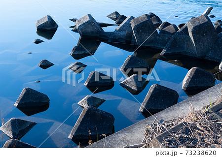透き通る、流れの穏やかな川と水から顔を出すテトラポッド 73238620