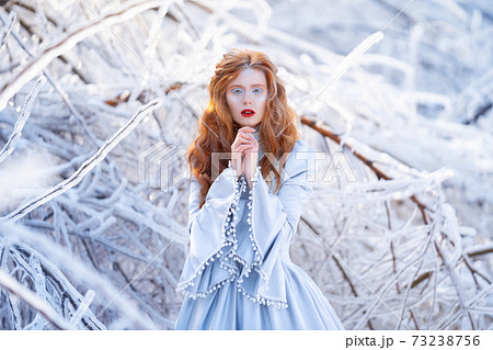 Young redhead woman, a princess, walks in a winter forest in a blue dress. 73238756