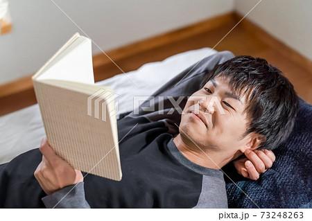 ステイホームで読書で充実する男性 73248263