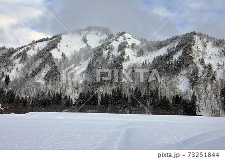 厳冬の里山と雪に埋まった田んぼ 福島県只見町 73251844