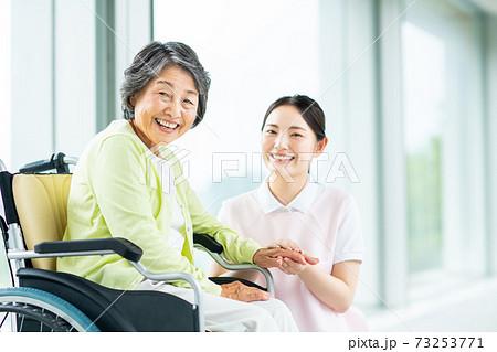 介護施設の高齢者と若い介護スタッフ 73253771