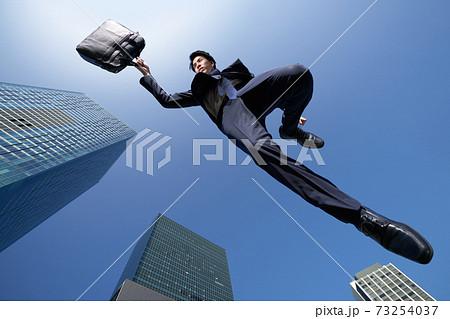 青空を背景にジャンプをするビジネスマン 73254037