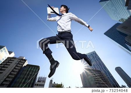 青空を背景にジャンプをするビジネスマン 73254048