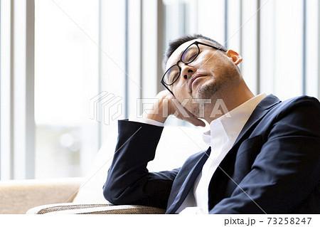 居眠りする男性 73258247
