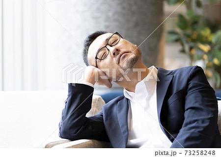 居眠りする男性 73258248