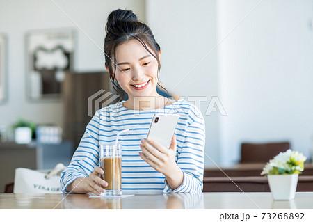カフェでスマホを見る若い女性 73268892