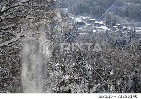 山形県峠道から見える山間の集落の風景と雪しずり 73286140