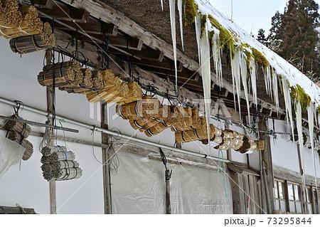 大内宿古民家の軒下に架かるマメコバチの巣筒につらら 73295844