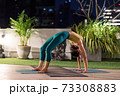 Asian woman do yoga in city at night 73308883