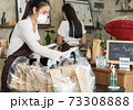Waitress with face mask prepare order for curbside pick up and takeout. 73308888