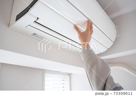 エアコンをメンテナンスする男性の手 73309011