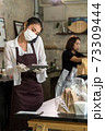 Waitress with face mask take order for curbside pick up and takeout. 73309444