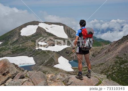 白山山頂から大汝峰を眺める登山者 73310343