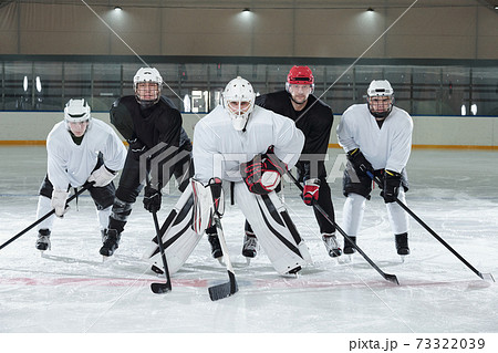 Professional hockey players bending forwards while standing on ice rink 73322039