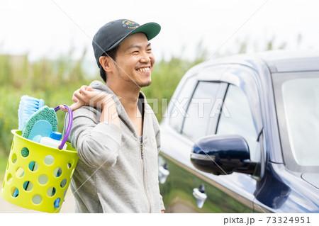 洗車で愛車が綺麗になることを楽しみに感じる男性 73324951