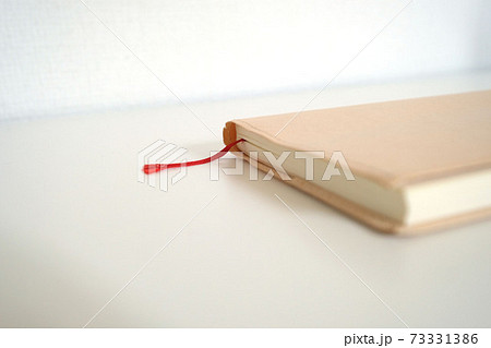 机に置かれている文庫本サイズのシンプルなノートと赤いしおり 73331386