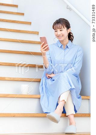 自宅の階段に座ってスマホを見る女性 73331489