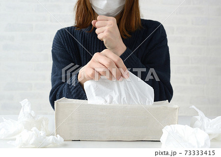 鼻水をかむためにティッシュをとる女性 73333415