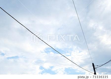 青空が垣間見える曇り空に伸びる3本の電線 73336335