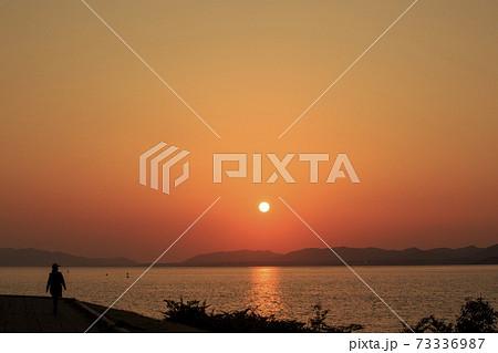 島根県 夕日の名所宍道湖の岸公園をウオーキングする人と夕日 73336987