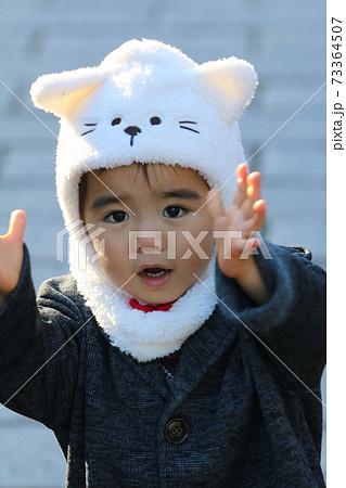 顔出し帽をかぶり両手を前に伸ばす2歳の男の子 73364507