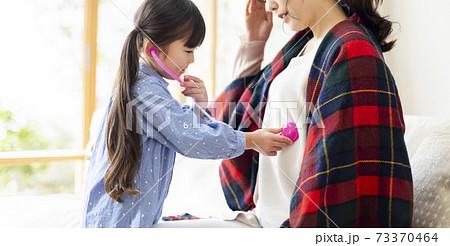体調不良のママを心配する女の子 73370464