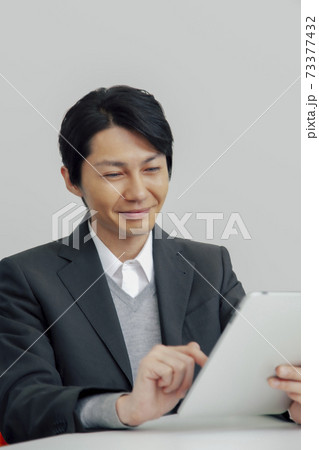 タブレットPCを操作するビジネスマン 73377432