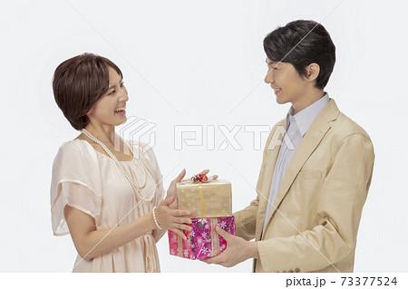 男性からプレゼントを受け取る女性 73377524