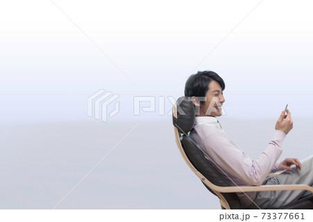 ソファに座ってスマートフォンの画面を見る男性 73377661