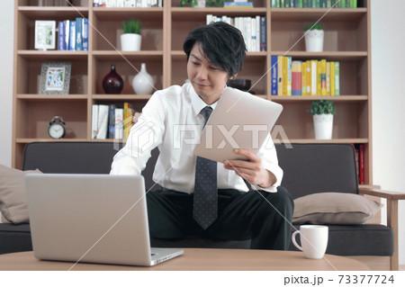 ソファに座ってタブレットPCとパソコンで仕事をする男性 73377724