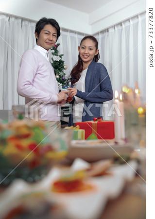 クリスマスツリーの前でプレゼントを持って立つ夫婦 73377820