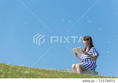 ベンチに座って本を読む笑顔の女性 73378053