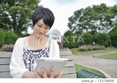 ベンチに座ってタブレットPCを操作する女性 73378606