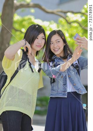 スマートフォンで写真を撮る女性2人 73378991