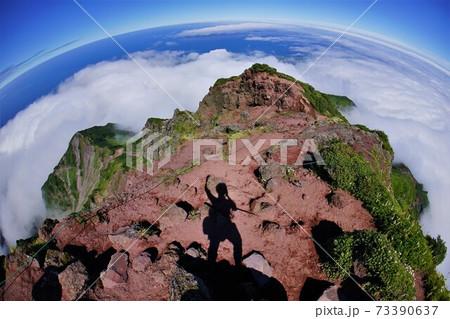 利尻山頂の岩稜帯に立つ登山者の影 73390637