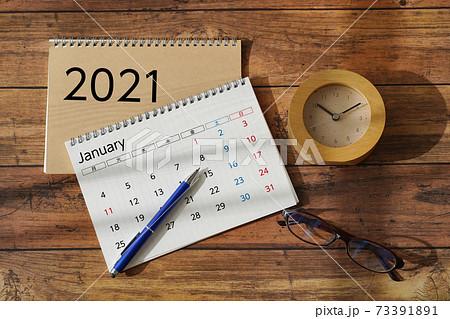 木目机に置かれたカレンダーと眼鏡と時計 73391891