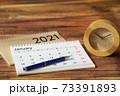 木目机に置かれたカレンダーとスケジュールと時計 73391893