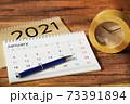 木目机に置かれたカレンダーとスケジュールと時計 73391894