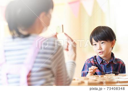 文字ブロックを見つめる幼い男の子 73408348