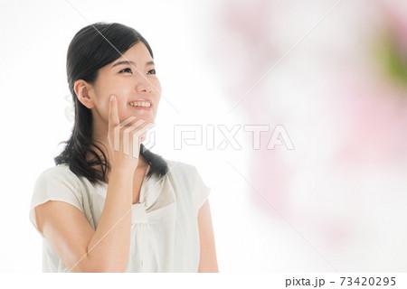 顔に人差し指をあてる笑顔の女性 春のイメージ 73420295