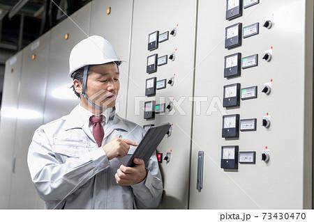 工場施設内の配電盤を確認するミドル男性 73430470