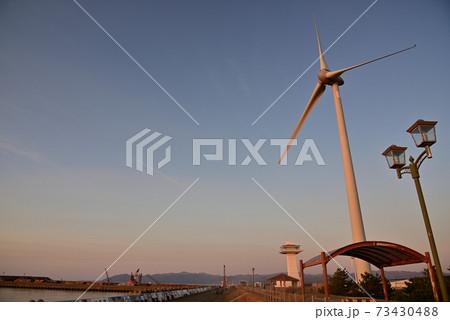 夕陽に照らされる風力発電機のある公園~能代港~ 73430488