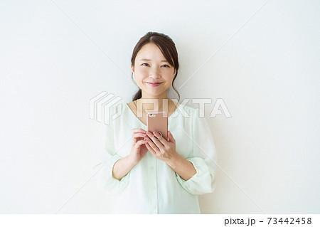 スマートフォンを見る女性 白背景 73442458