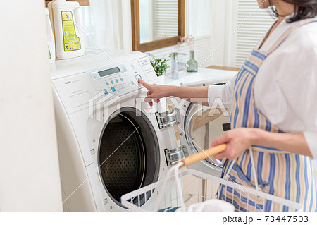 洗濯機に洗濯物を入れるミドル女性 73447503