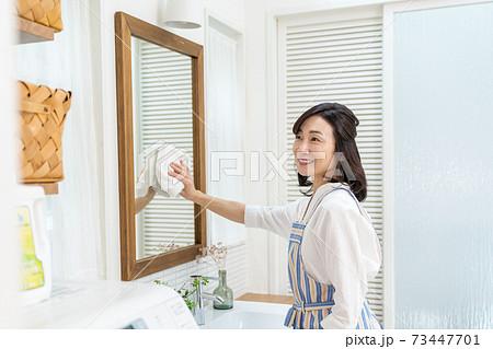 鏡を掃除するミドル女性 73447701